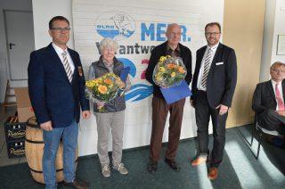 (Foto: DLRG Lübeck): Auszeichnung für langjährige Mitglieder (v.l.) Henning Otto (Geschäftsführer und stellv. Vorsitzender), Anke-Marie Lohrisch (65 Jahre Mitgliedschaft), Peter Saldigkt (60 Jahre Mitgliedschaft und Thomas Becker (Vorsitzender)
